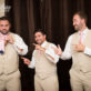 Groomsmen and Groom putting on tie