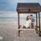Engaged couple on a bench at the beach